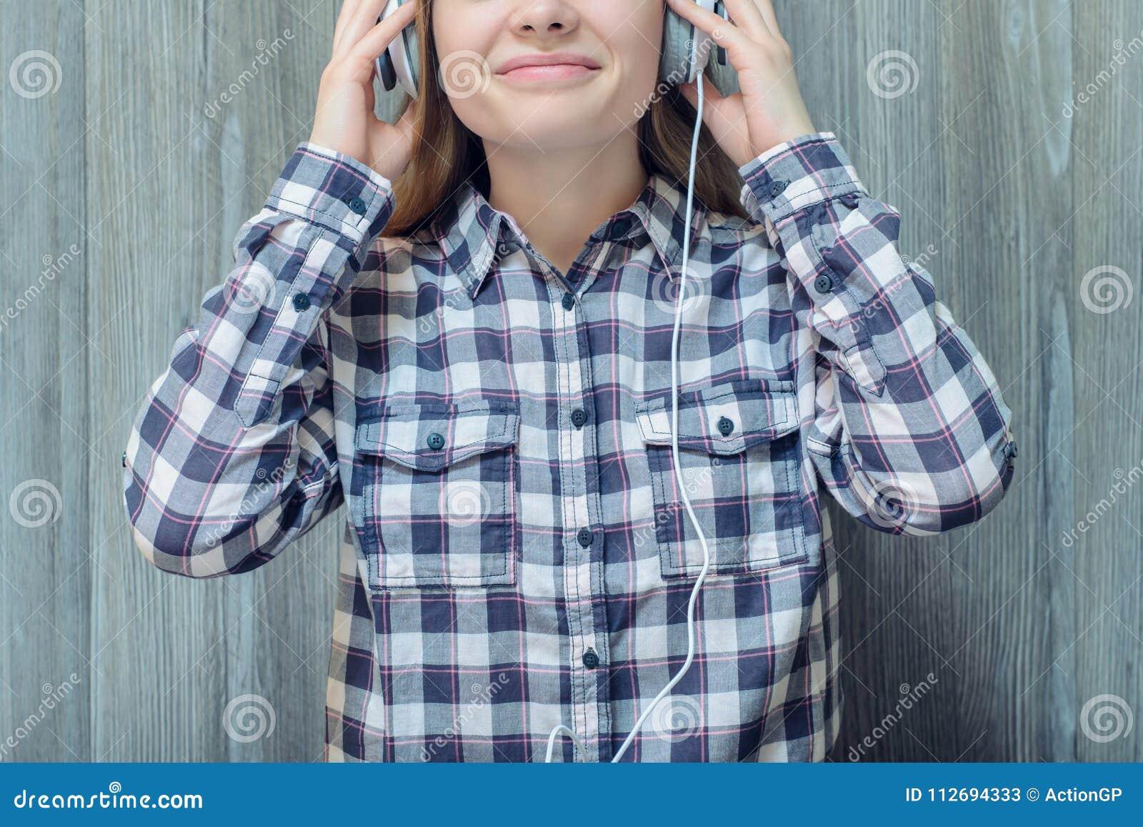 Jonge tiener in geruit overhemd wat betreft hoofdtelefoons en Li