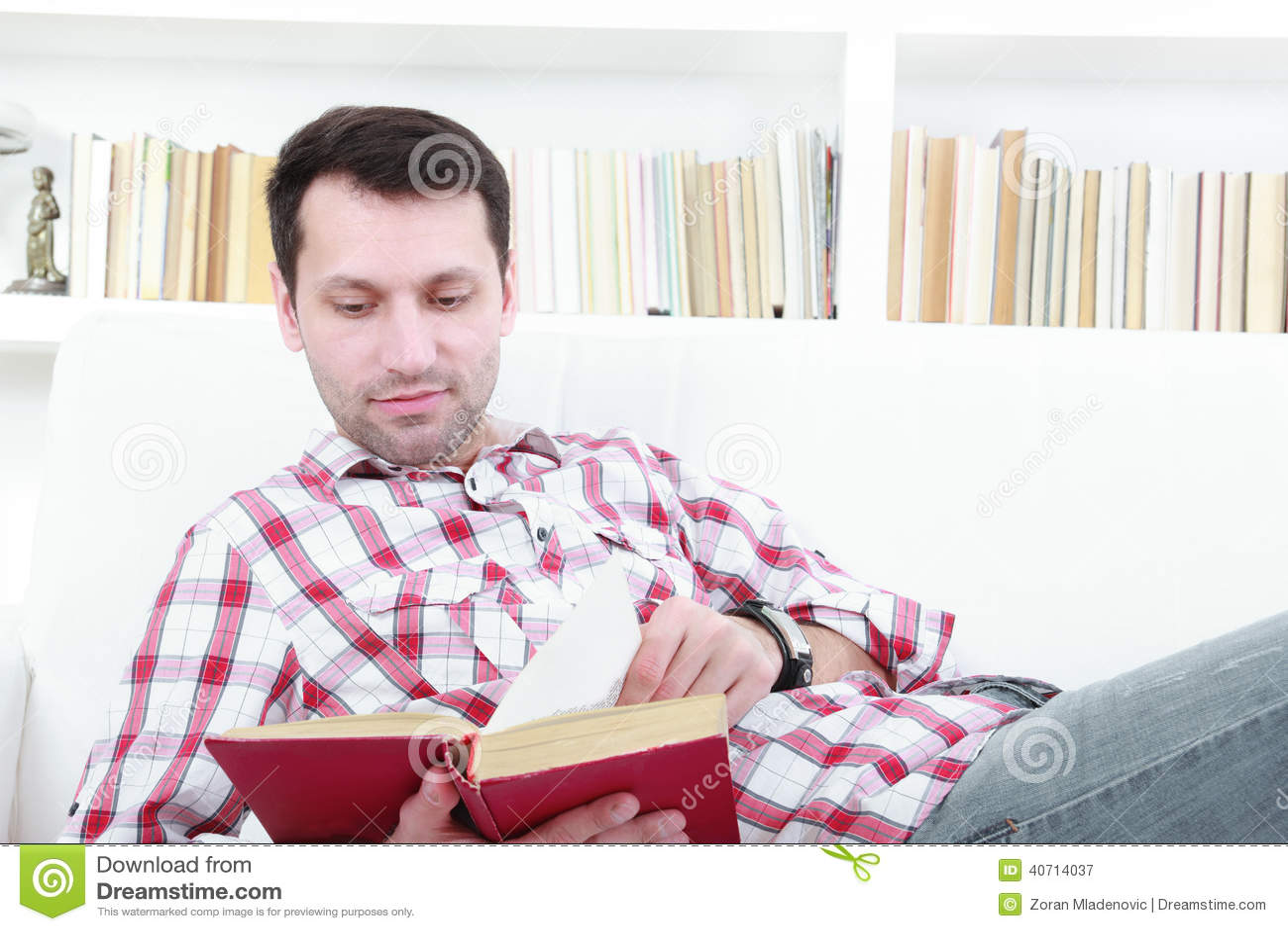 Jonge toevallige mens die boek het ontspannen op bank lezen
