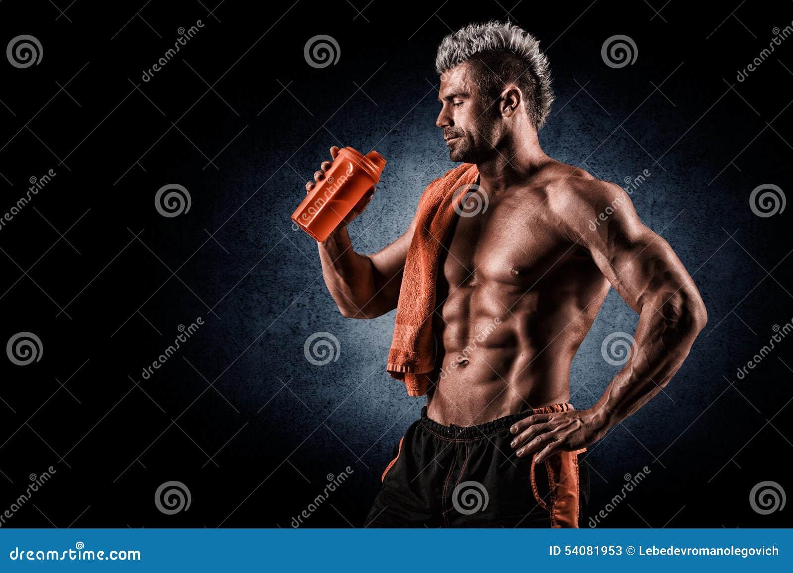Jonge volwassen mens die eiwitschok in gymnastiek drinken Zwarte achtergrond