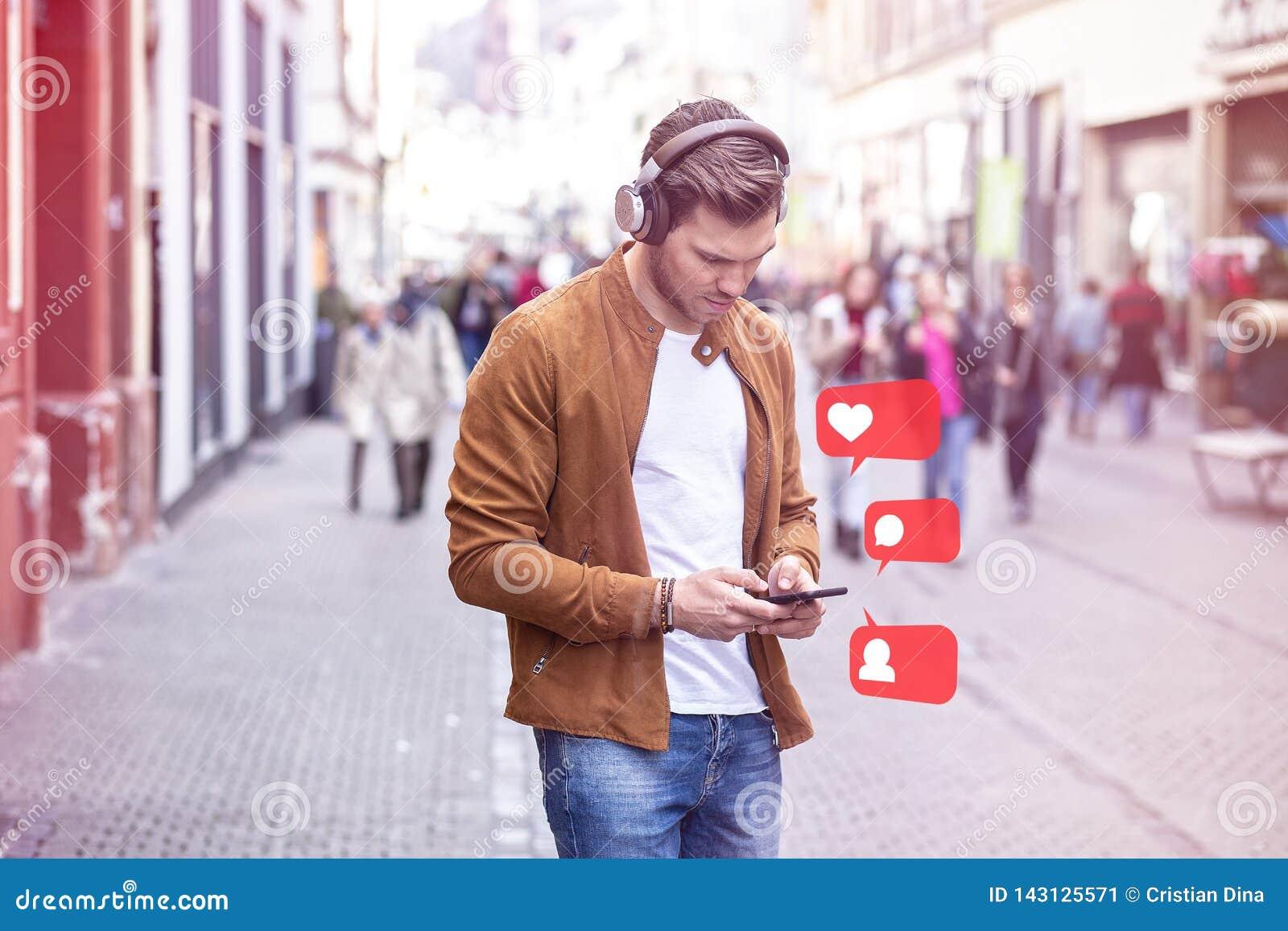 Jonge Volwassen Mens het Luisteren Muziek op Smartphone en Hoofdtelefoon op de Straat in de Zomertijd