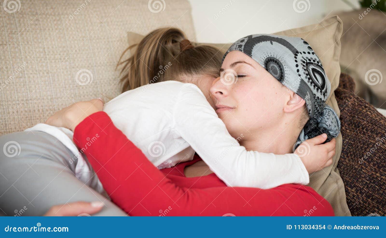 Jonge volwassen vrouwelijke kanker geduldige het besteden tijd met haar dochter die thuis, op de laag ontspannen