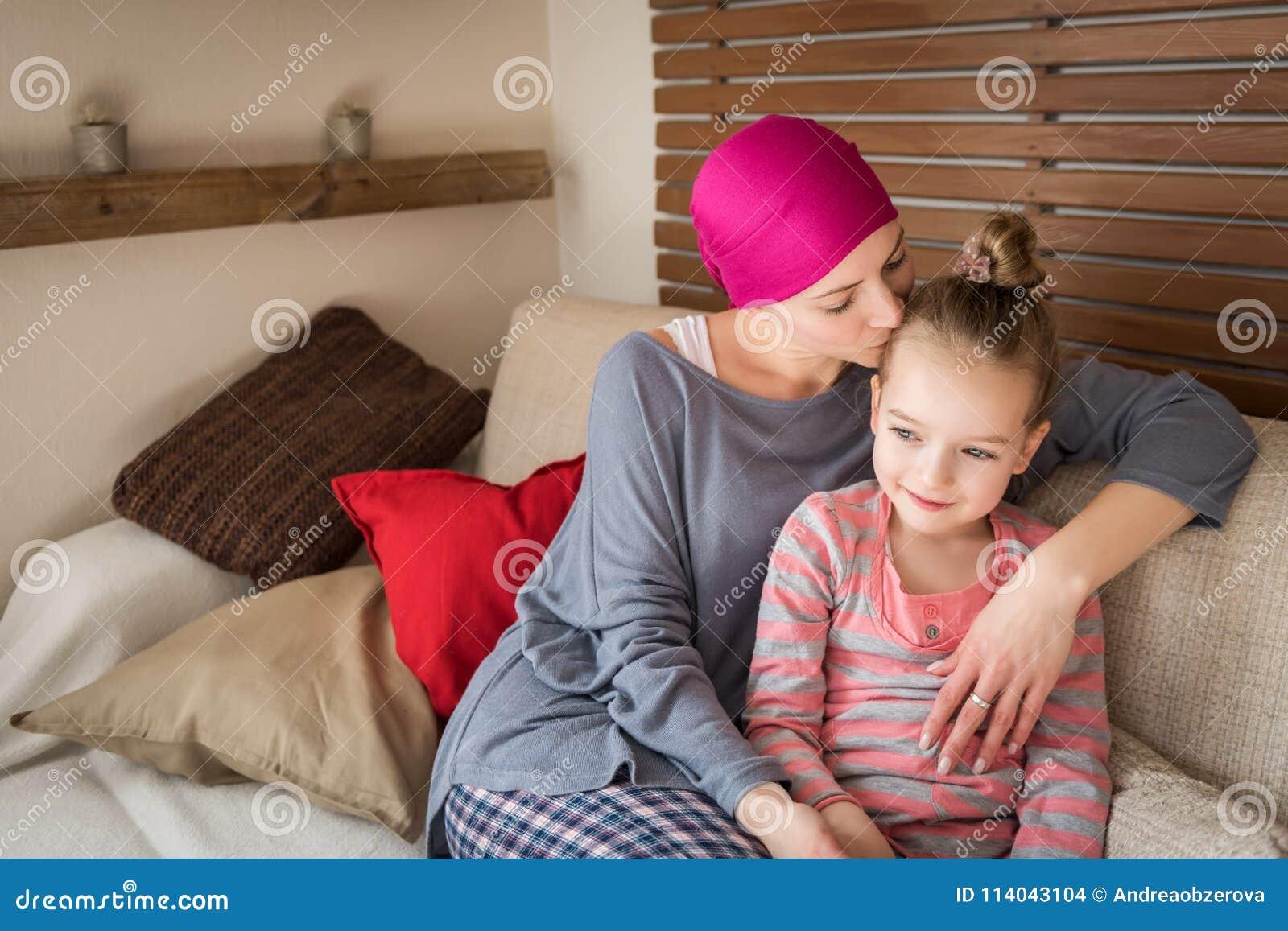 Jonge volwassen vrouwelijke kanker geduldige het besteden tijd met haar dochter die thuis, op de laag ontspannen Kanker en famili