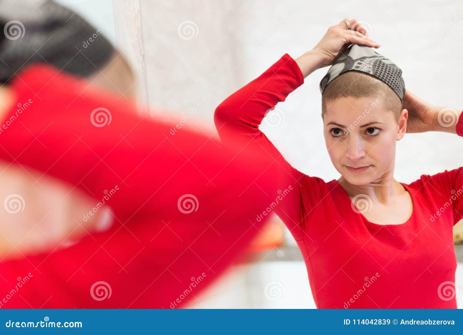 Jonge volwassen vrouwelijke kankerpatiënt die haar headscarf aanpassen die in de spiegel kijken Vermoeide, uitgeputte, gedeprimee