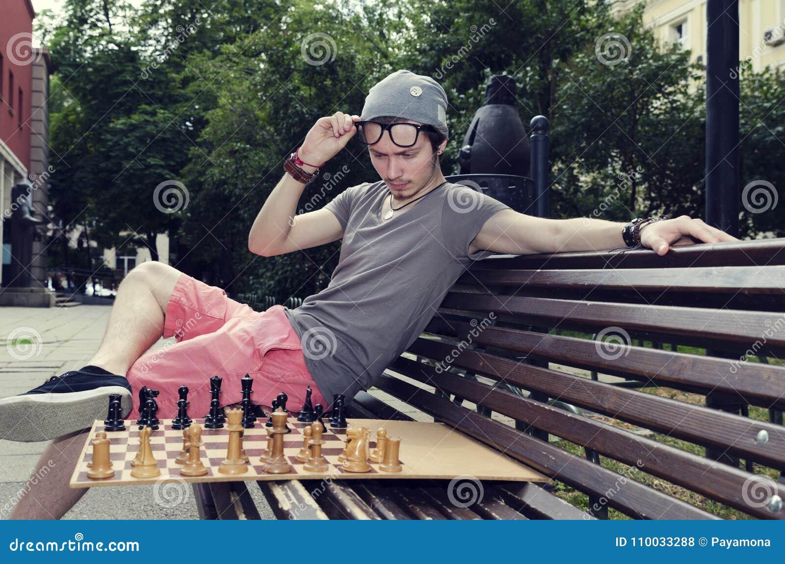 Jonge volwassen zitting op een een bank en het spelen schaak