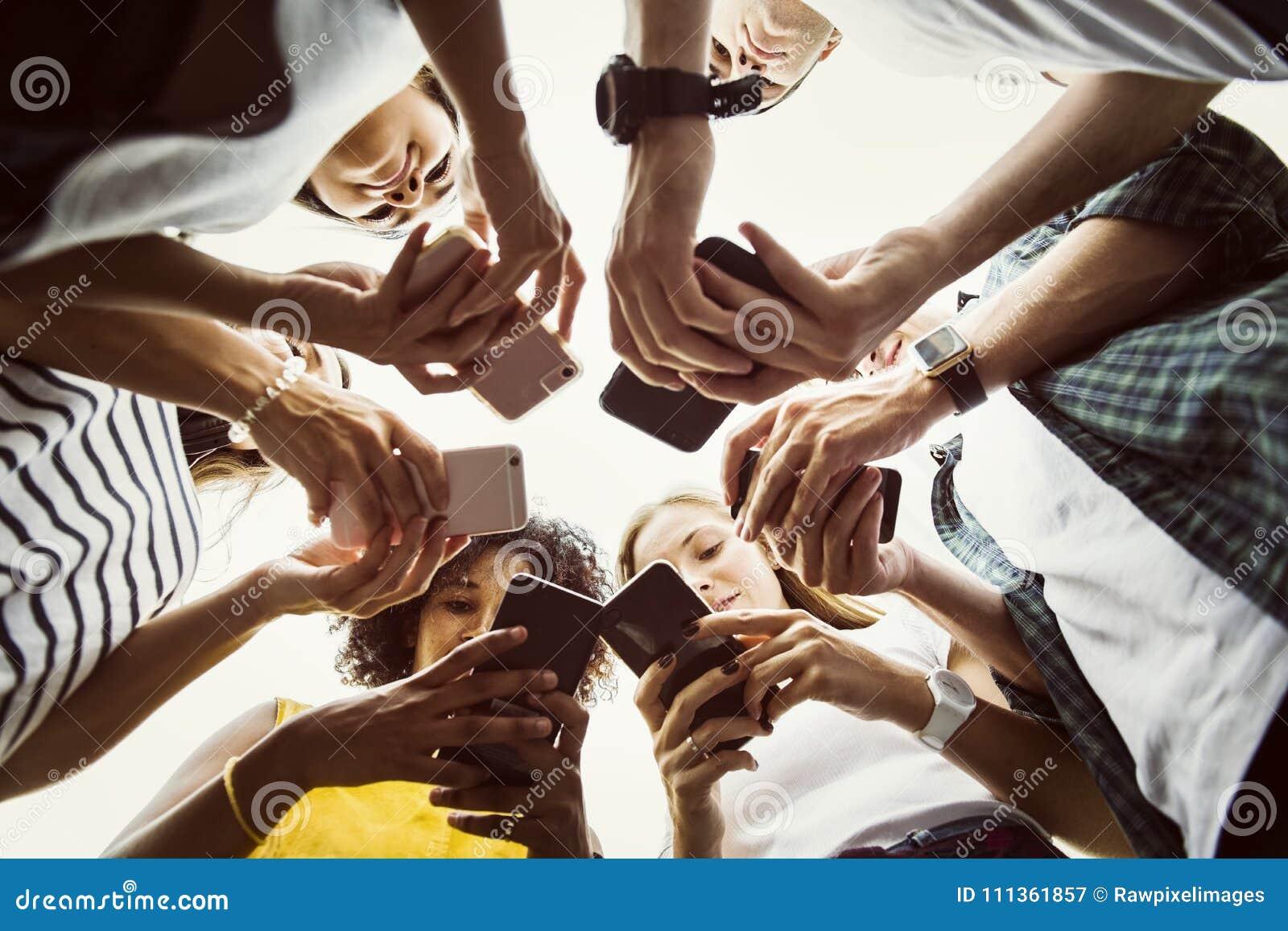 Jonge volwassenen die smartphones in een cirkel sociale media gebruiken en conn