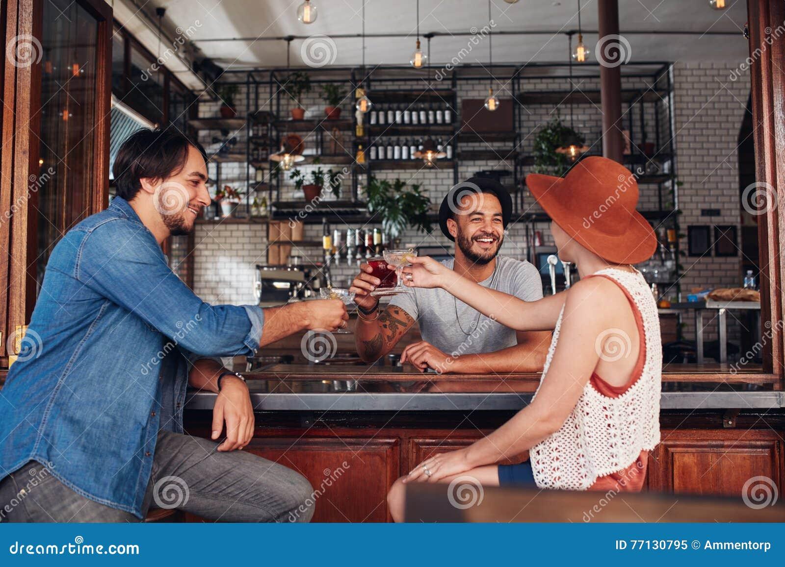 Jonge vrienden bij koffie roosterende dranken