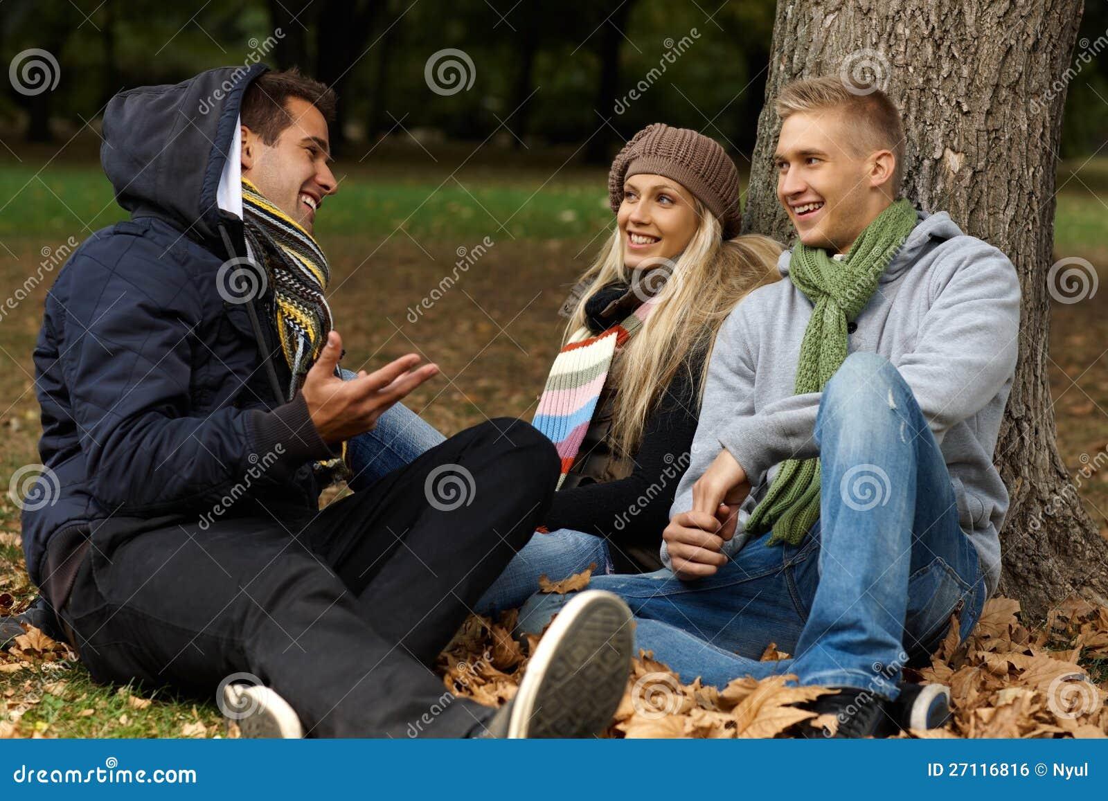 Jonge vrienden die op grond in de herfstpark zitten