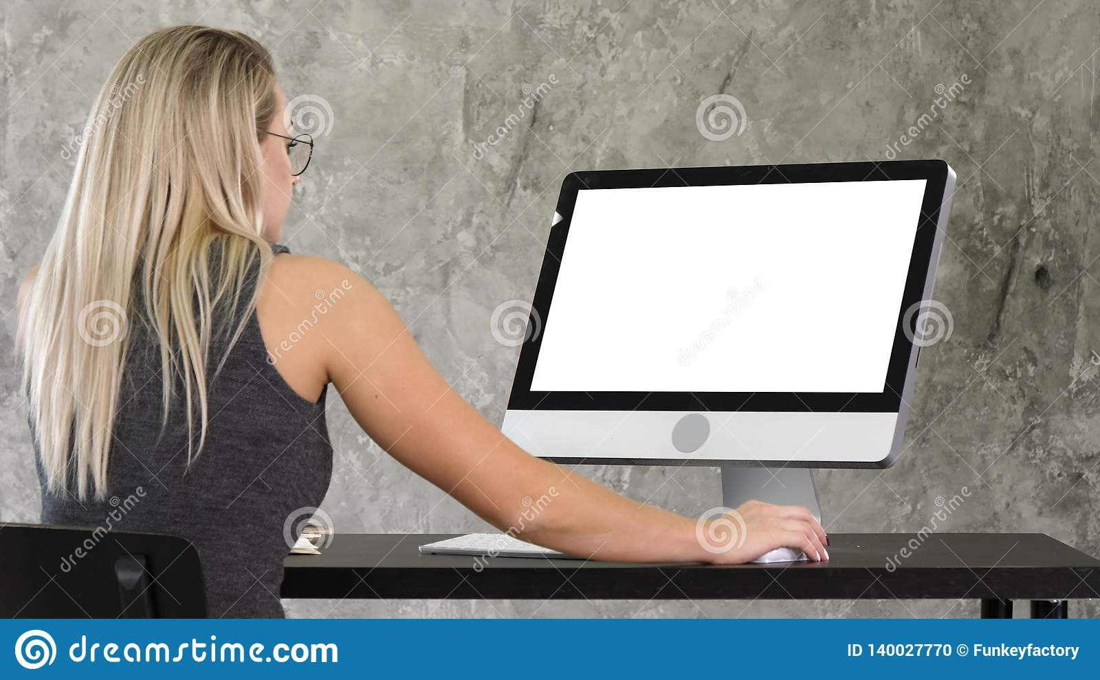 Jonge vriendschappelijke exploitantvrouw die en aan de computer spreken werken Witte vertoning