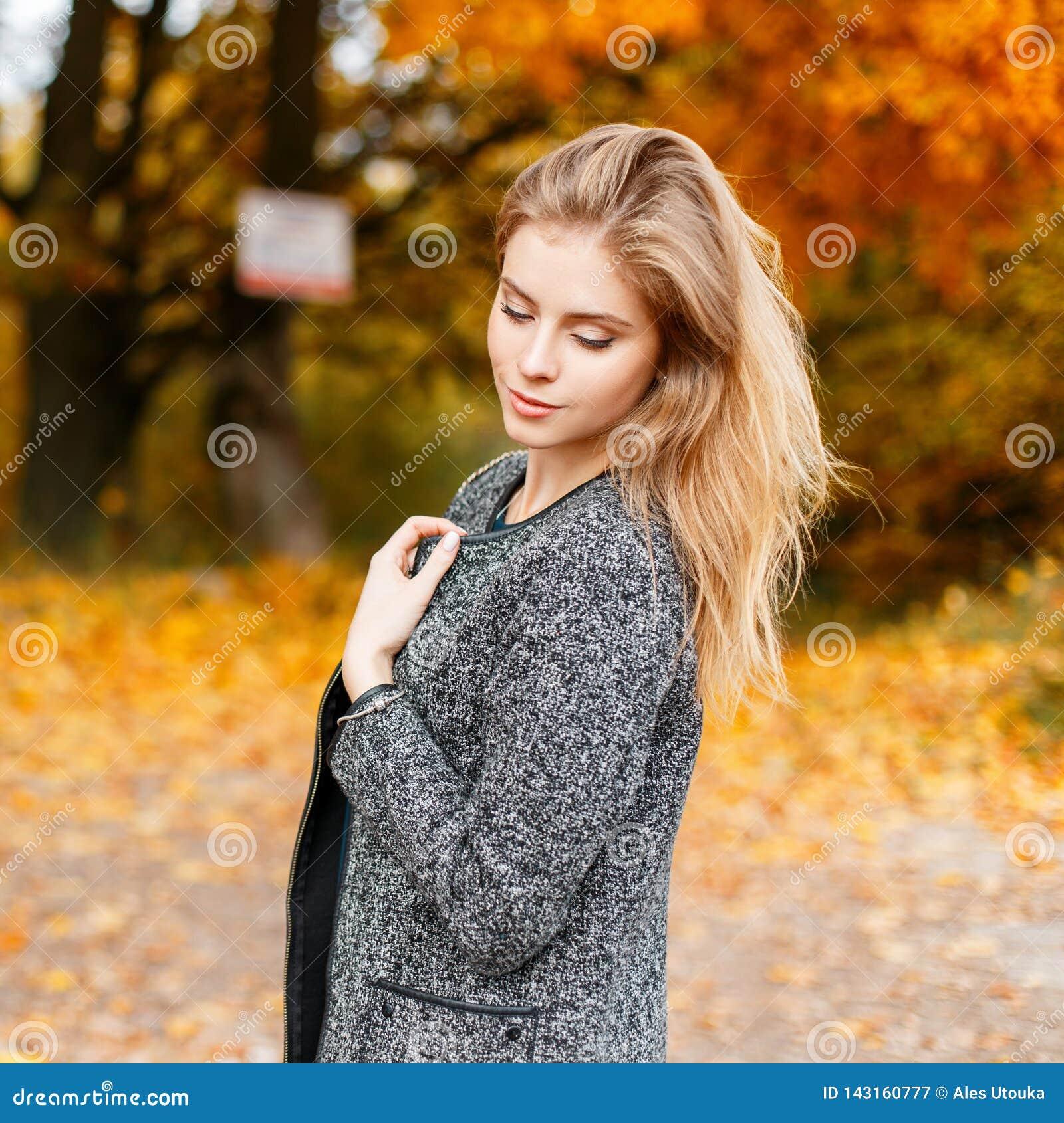 Jonge vrij aantrekkelijke modieuze vrouw in een grijze elegante laag die in openlucht in een park rusten De modieuze meisjesmanne