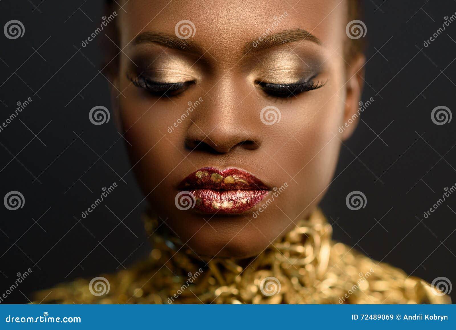 Jonge vrij Afrikaanse die vrouw, met haar in kapsel en gevoelige gouden samenstelling wordt verzameld, die op zwarte achtergrond
