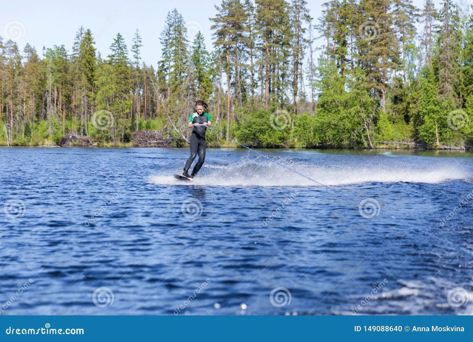 Jonge vrij slanke donkerbruine vrouw in wetsuit die wakeboard op golf van motorboot berijden
