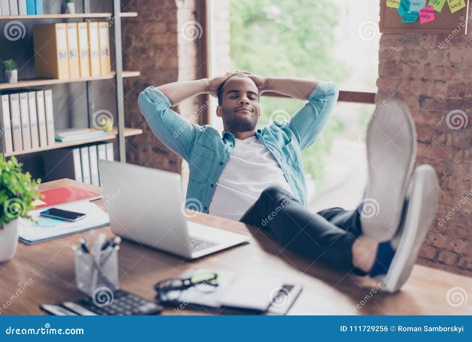 Jonge vrolijke afro freelancer rust op het werk, met voeten bovenop het bureau, met gesloten ogen, het glimlachen, het dromen