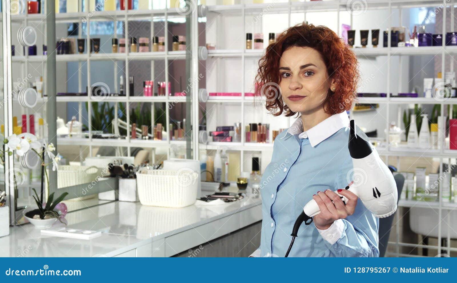 Jonge vrolijke beautful vrouwelijke kapper bij haar werkplaats bij de salon