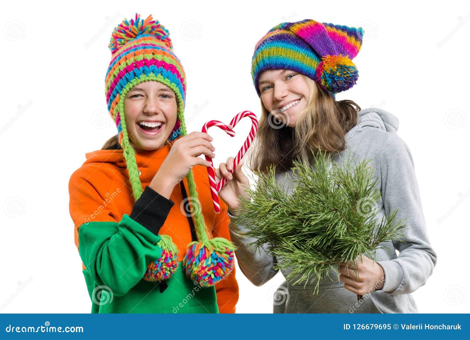 Jonge vrolijke tieners die pret met het riet van het Kerstmissuikergoed, in de winter gebreide die kappen hebben, op witte achter