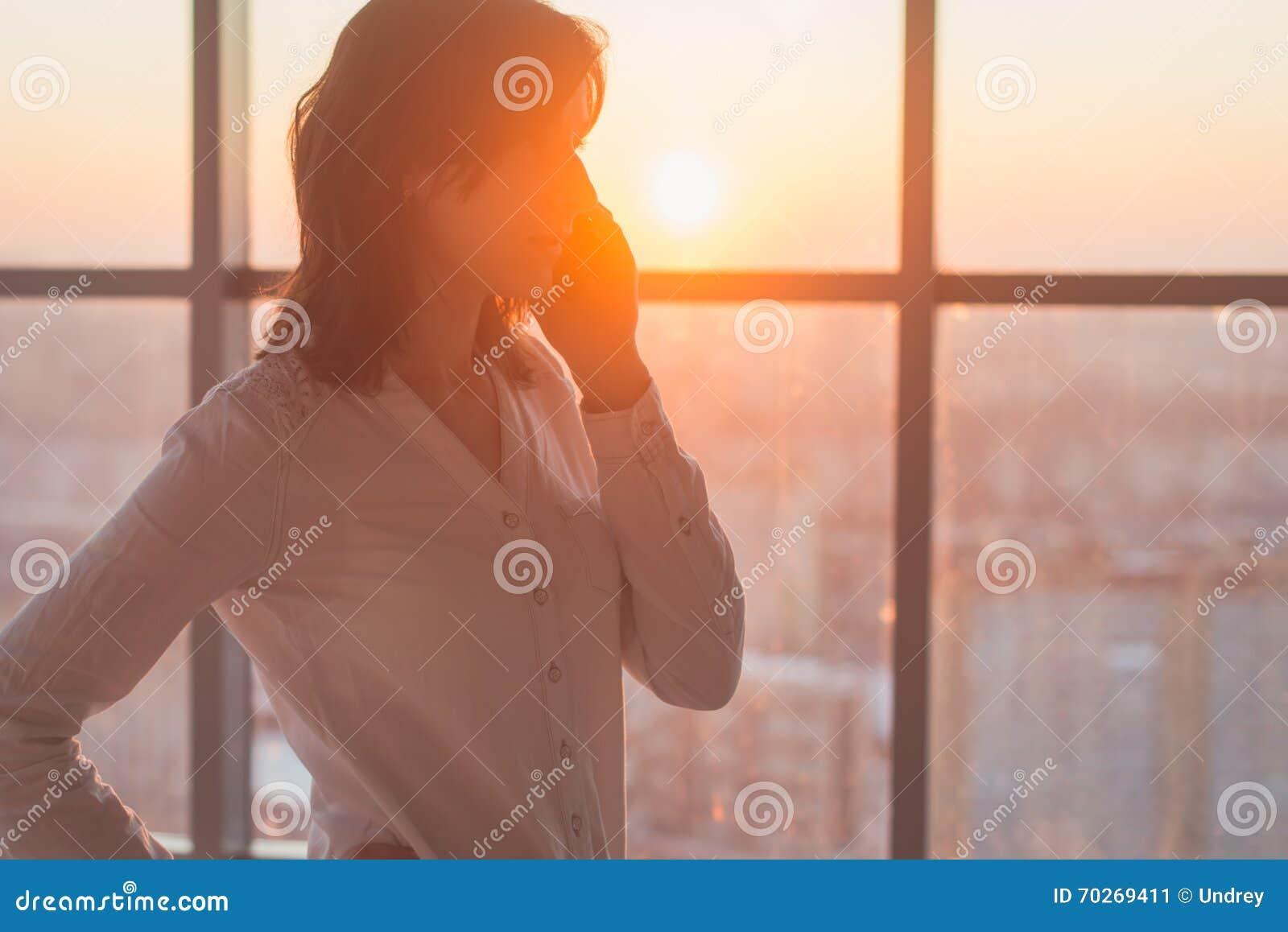 Jonge vrouw bezig met roepen, die op het het zijaanzichtportret van de celtelefoon babbelen Close-upbeeld van een onderneemster