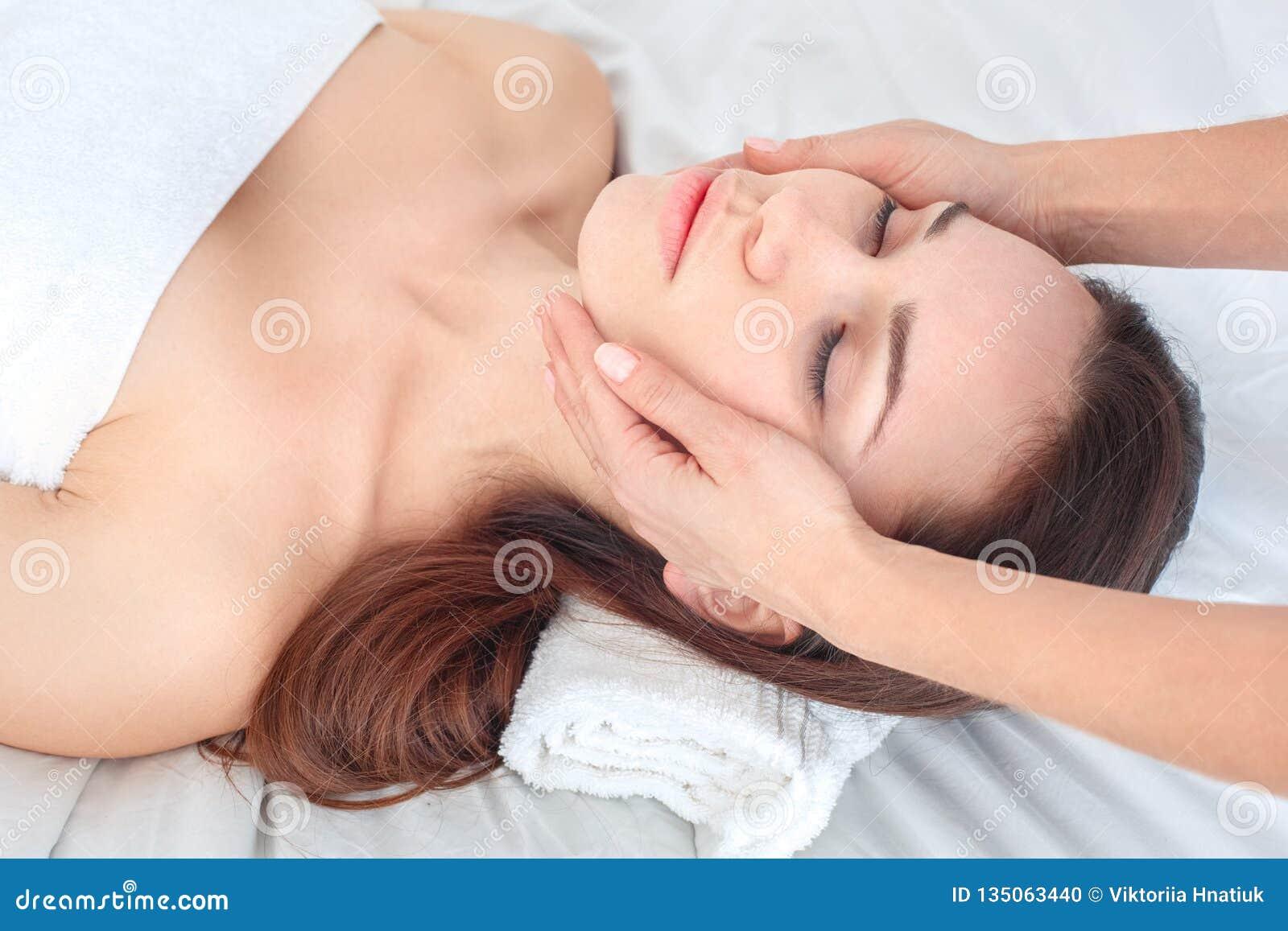 Jonge vrouw bij schoonheidssalon die krijgend het close-up van de gezichtsmassage liggen