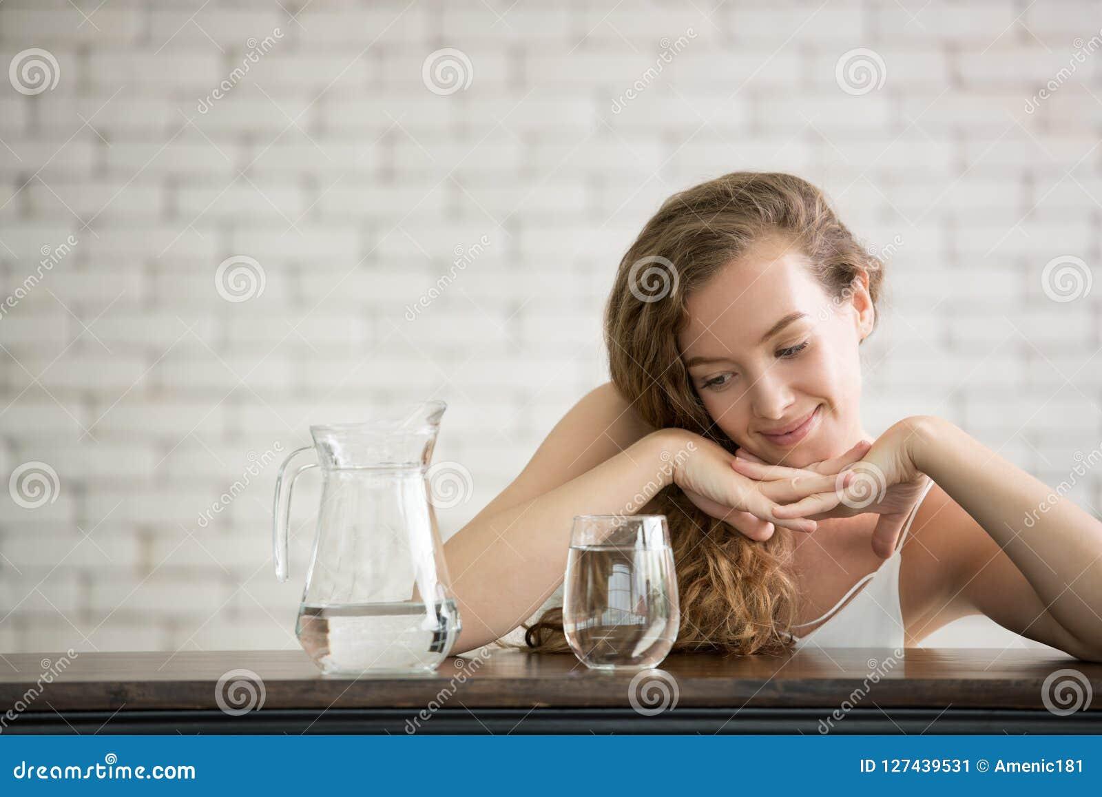 Jonge vrouw in blije houdingen met kruik en glas drinkwater
