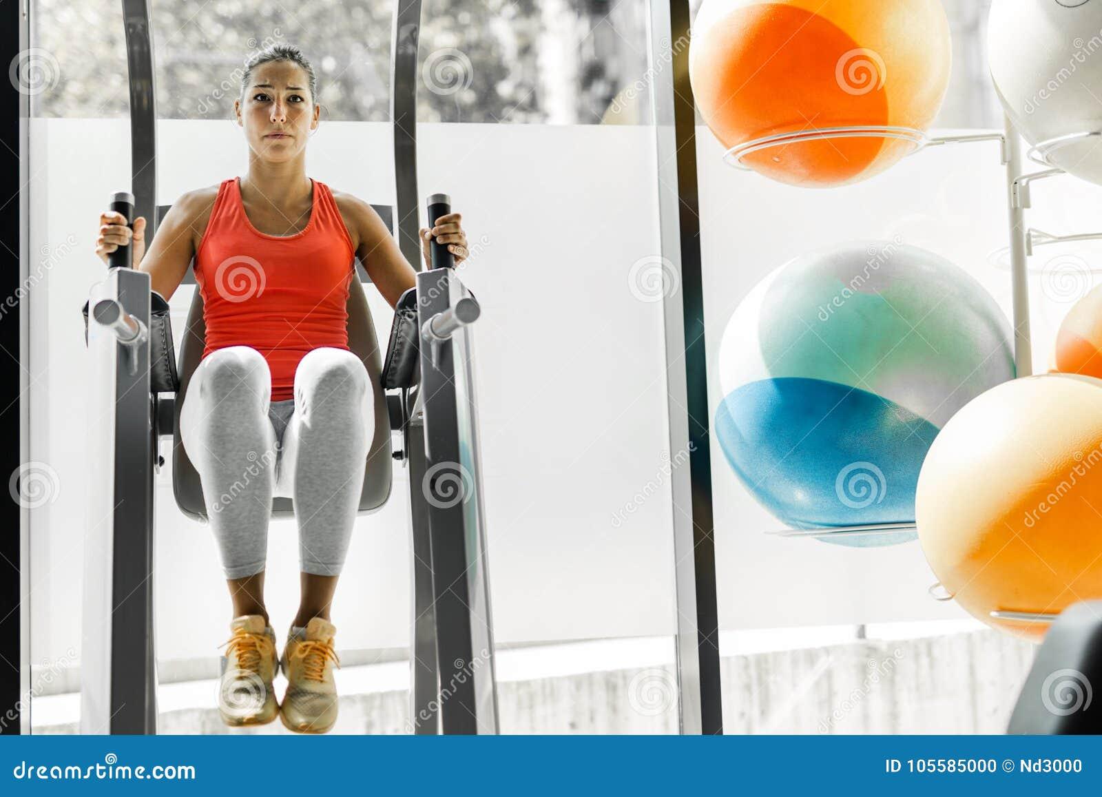 Jonge vrouw die aan abs in een gymnastiek werken