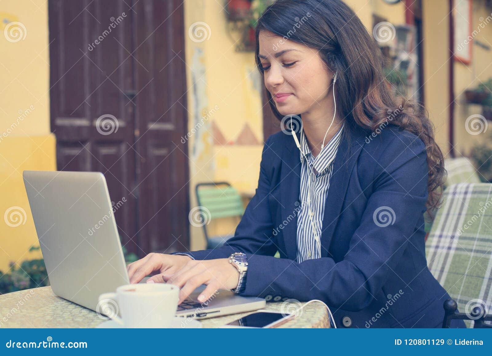 Jonge vrouw die aan laptop, het luisteren muziek werken