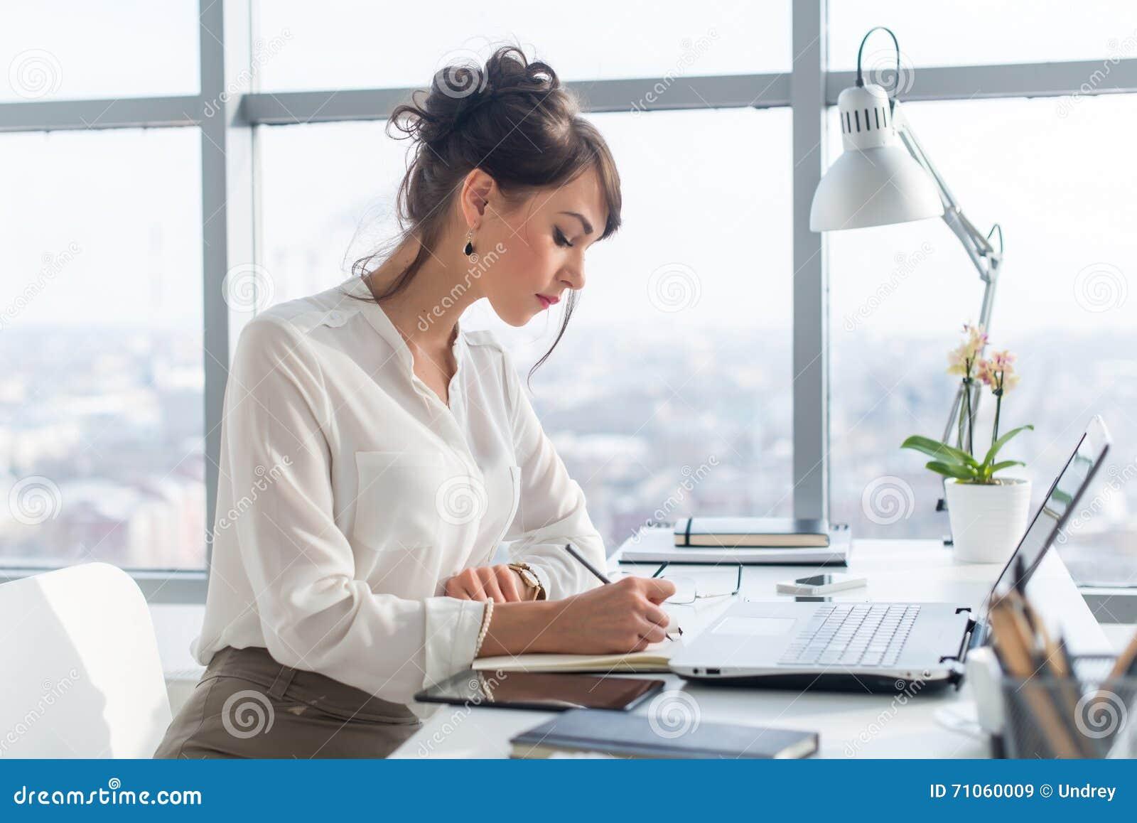 Jonge vrouw die als bureaumanager werken, de taken van het planningswerk, die haar programma neerschrijven aan ontwerper op het w