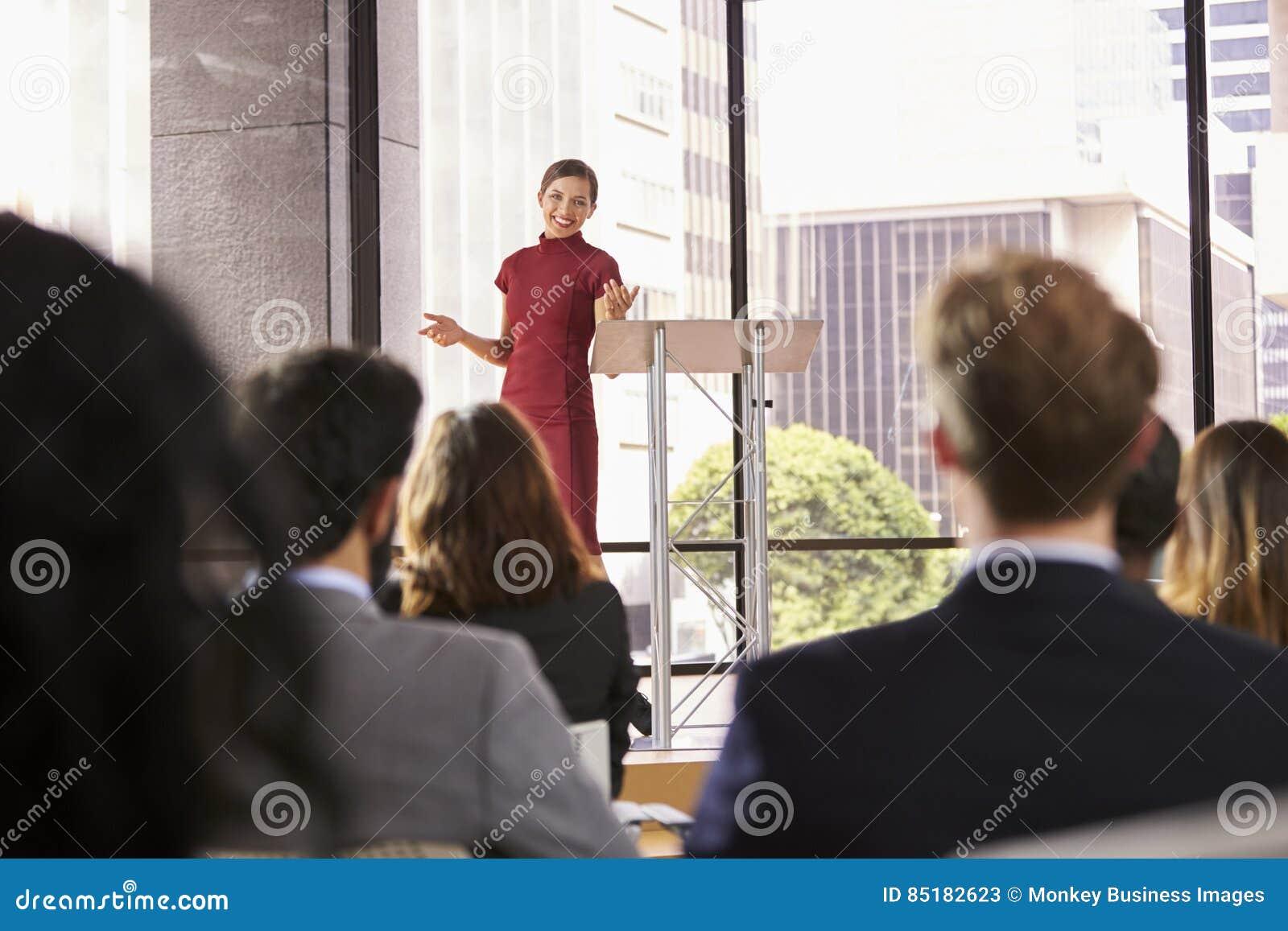Jonge vrouw die bedrijfsseminariegebaren voorstellen aan publiek