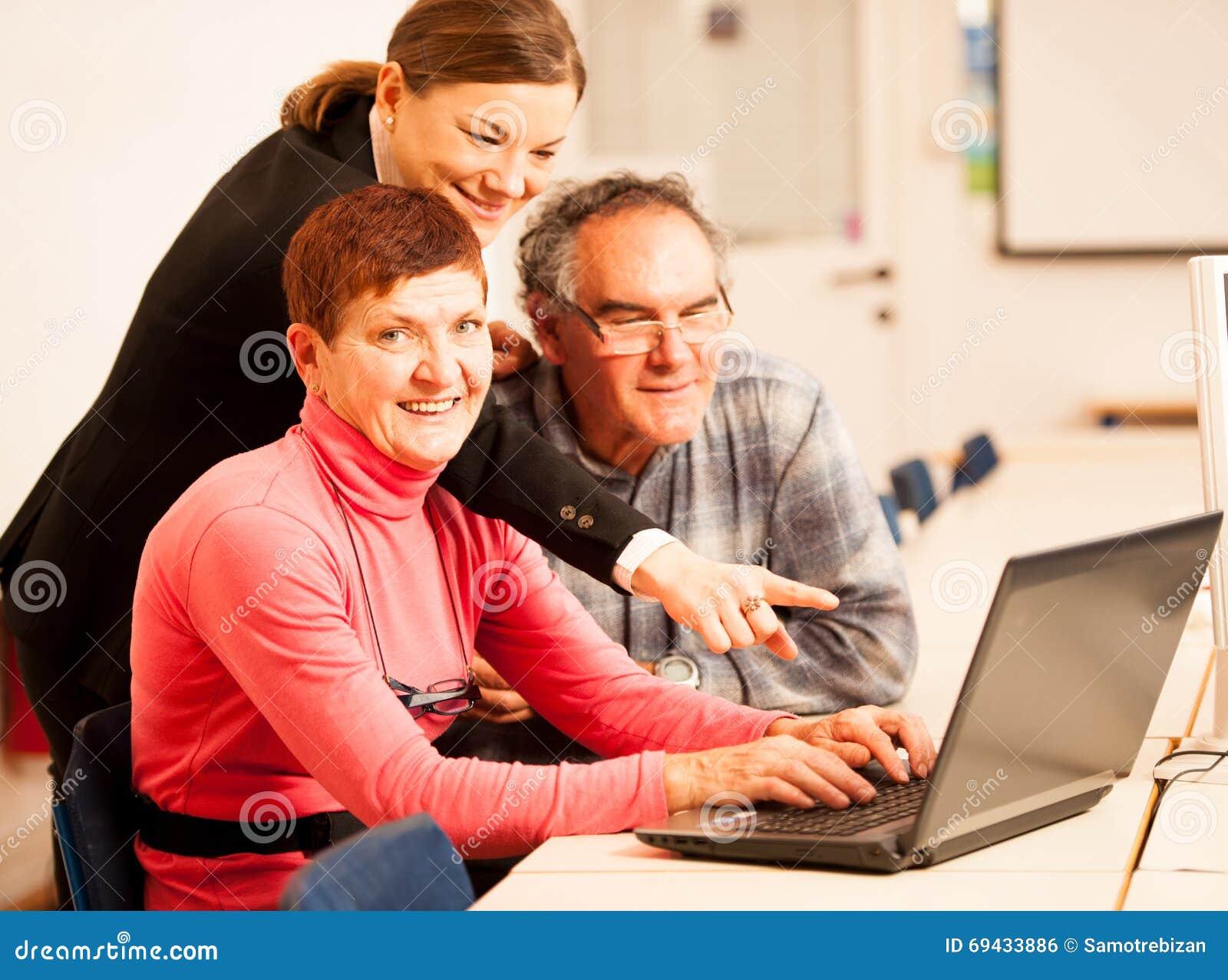 Jonge vrouw die bejaard paar van computervaardigheden onderwijzen Intergen