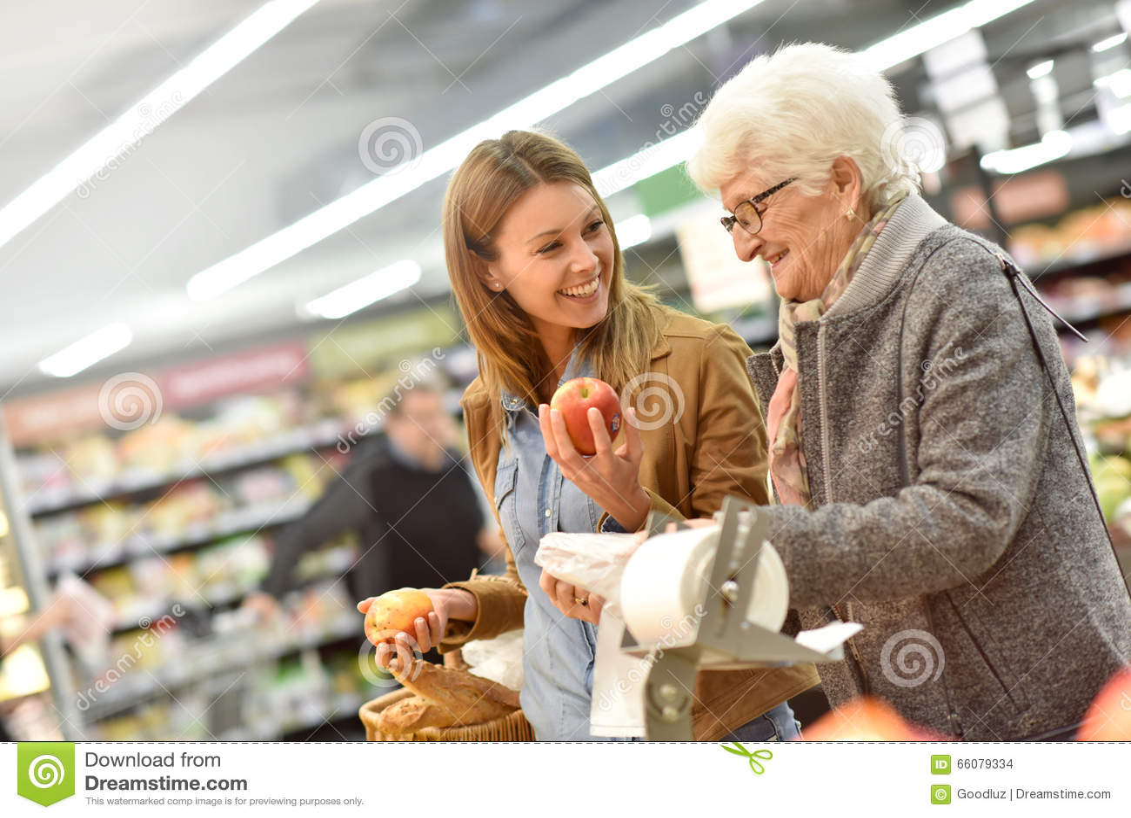 Jonge vrouw die bejaarden met kruidenierswinkels helpen