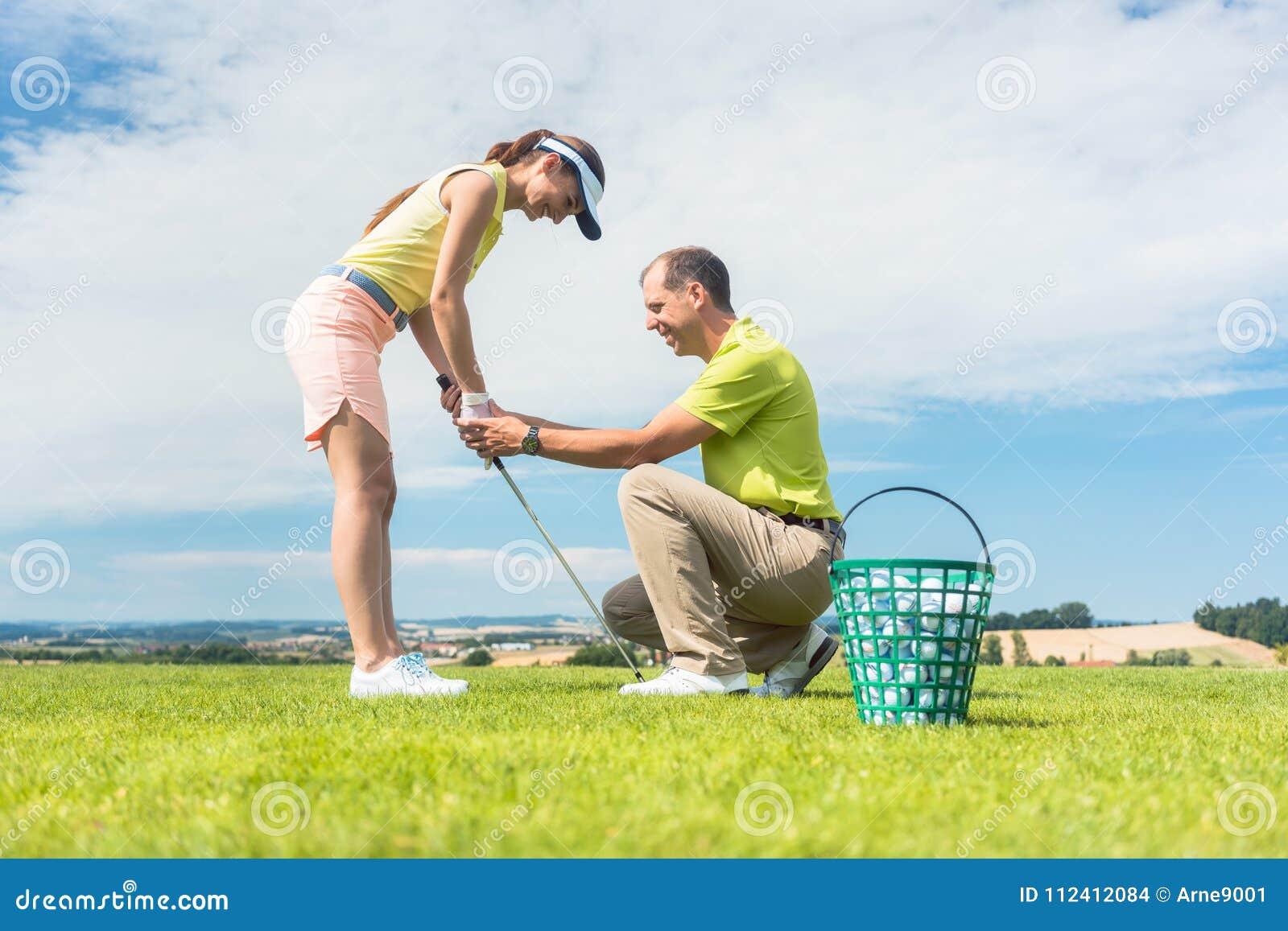 Jonge vrouw die die de golfschommeling uitoefenen door haar instructeur wordt geholpen