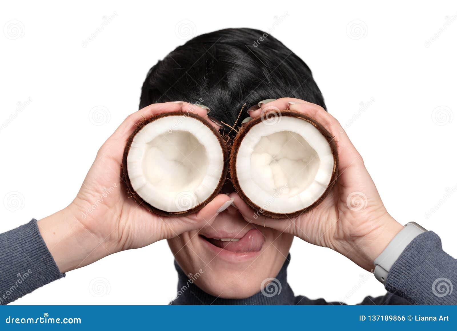 Jonge vrouw die de twee helft van kokosnoot voor ogen houdt