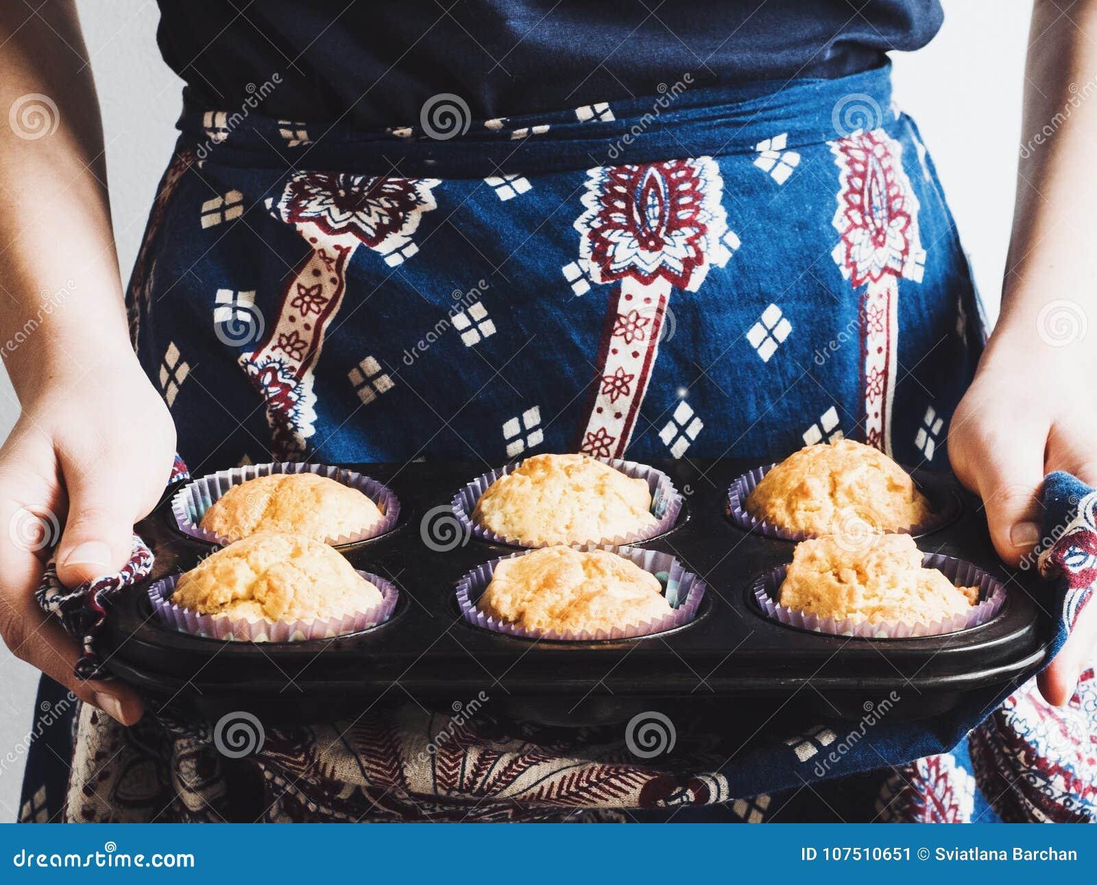Jonge vrouw die een dienblad van geurige cupcakes houden
