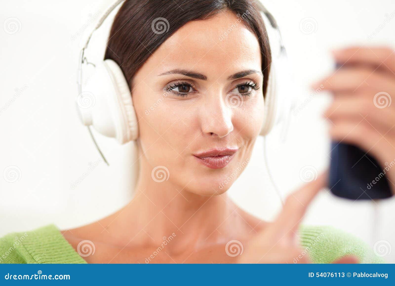 Jonge vrouw die een draagbare muziekspeler met behulp van