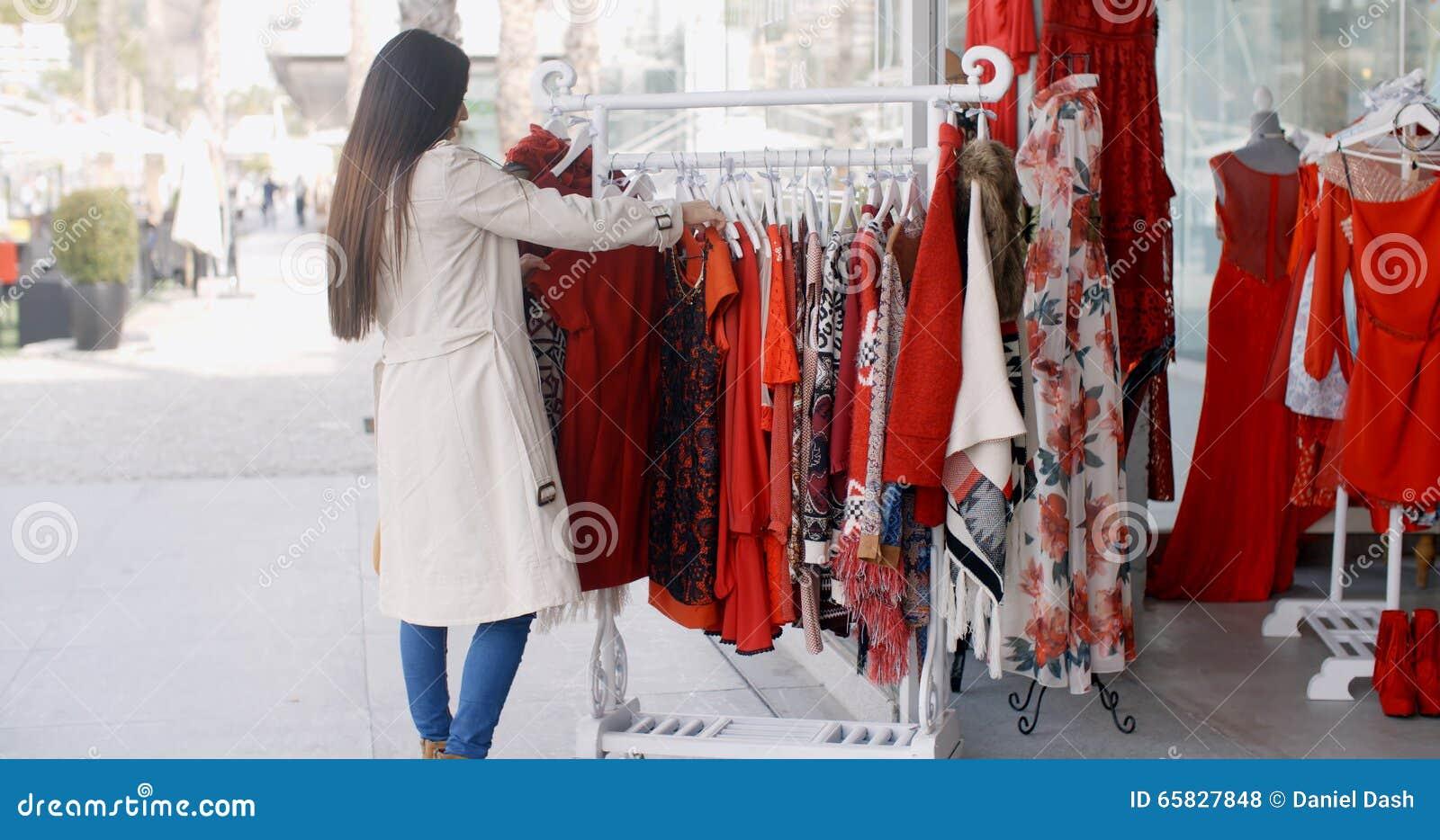 Kleding Zoeken.Jonge Vrouw Die Een Kleurrijke Rode Kleding Zoeken Stock Foto