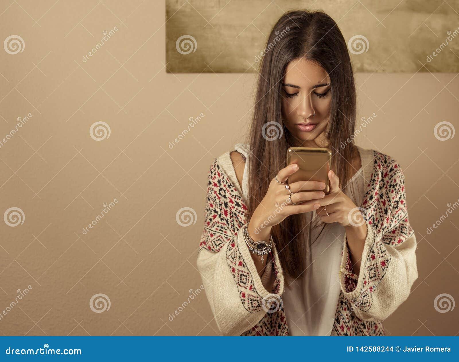 Jonge vrouw die een mobiele telefoon met behulp van