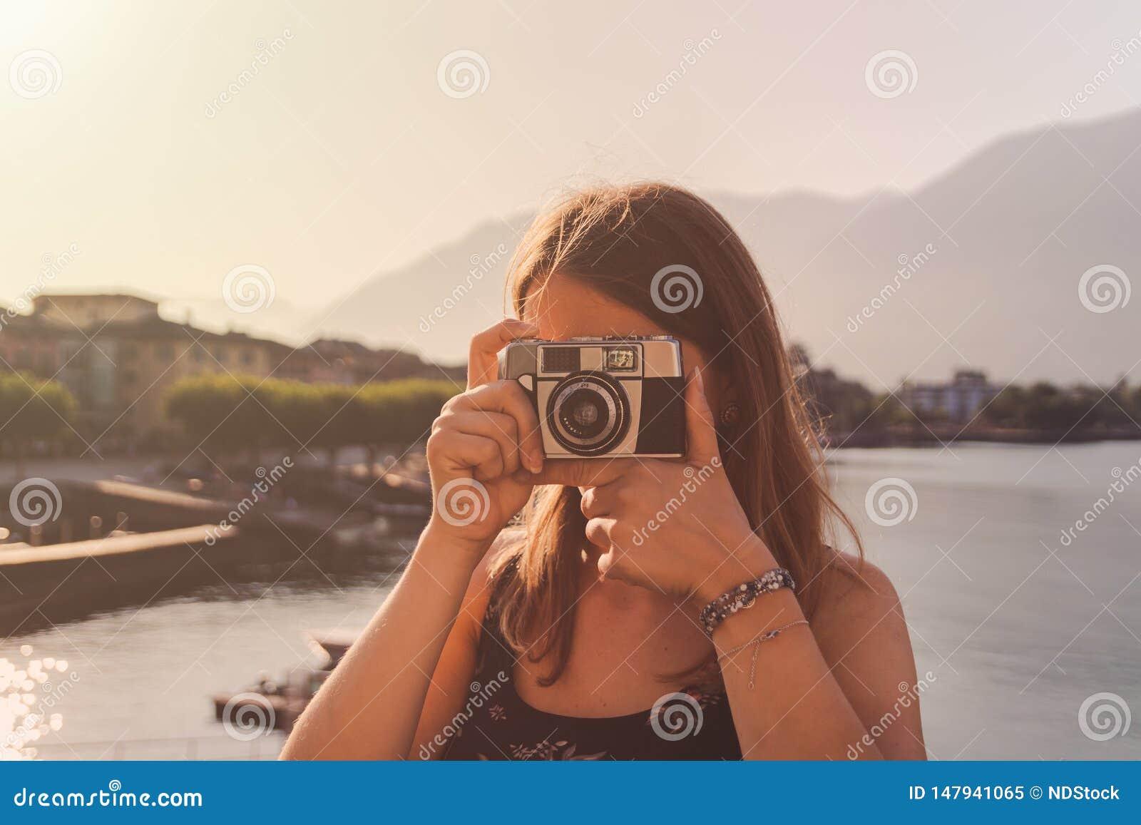 Jonge vrouw die een uitstekende camera voor de meerpromenade met behulp van in Ascona