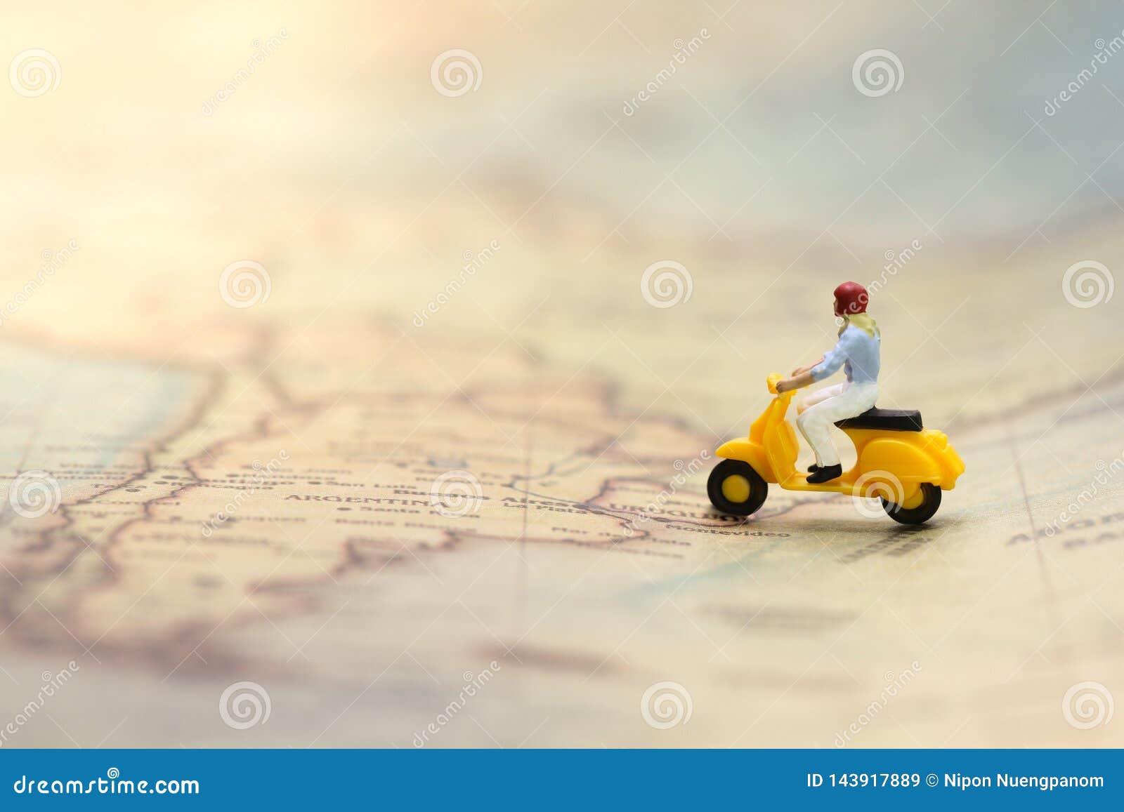 Jonge vrouw die gele cijferautoped berijden op uitstekende wereldkaart