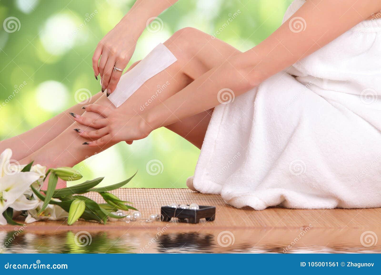 Jonge vrouw die haar benen in de was zetten