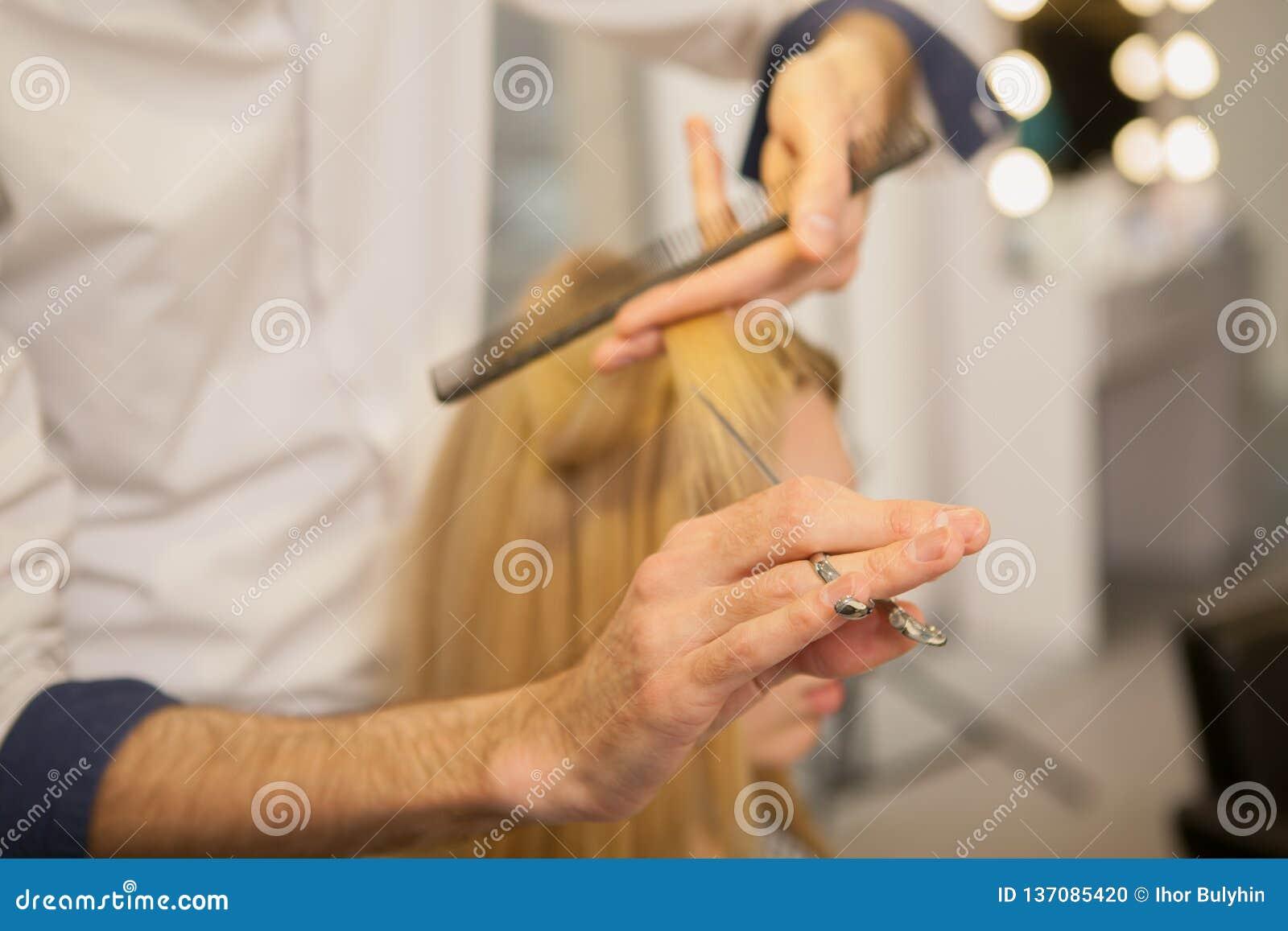 Jonge vrouw die haar die haar hebben door kapper wordt gestileerd