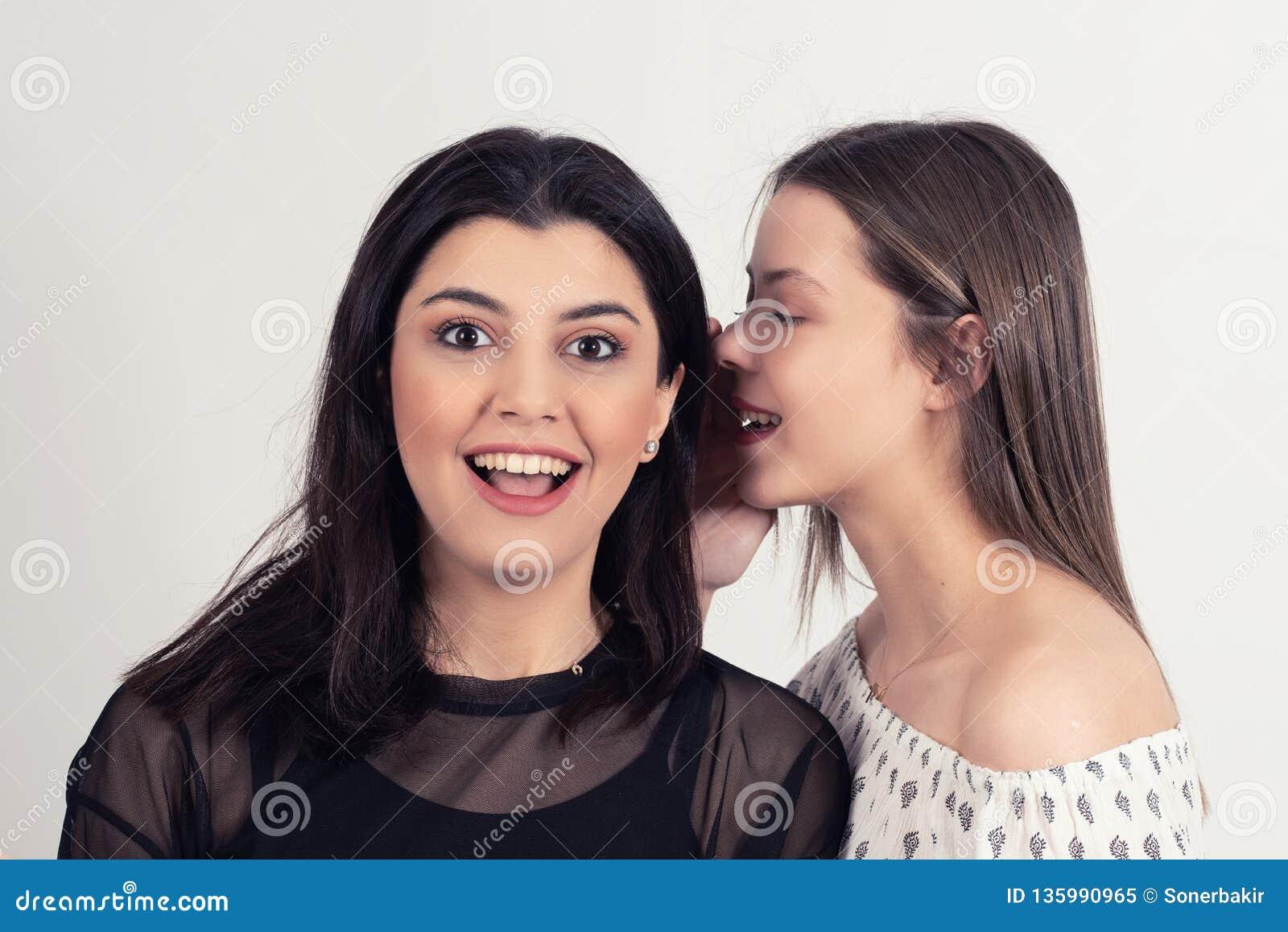 Jonge vrouw die haar meisje één of ander geheim vertellen Het Roddelen van twee Vrouwen
