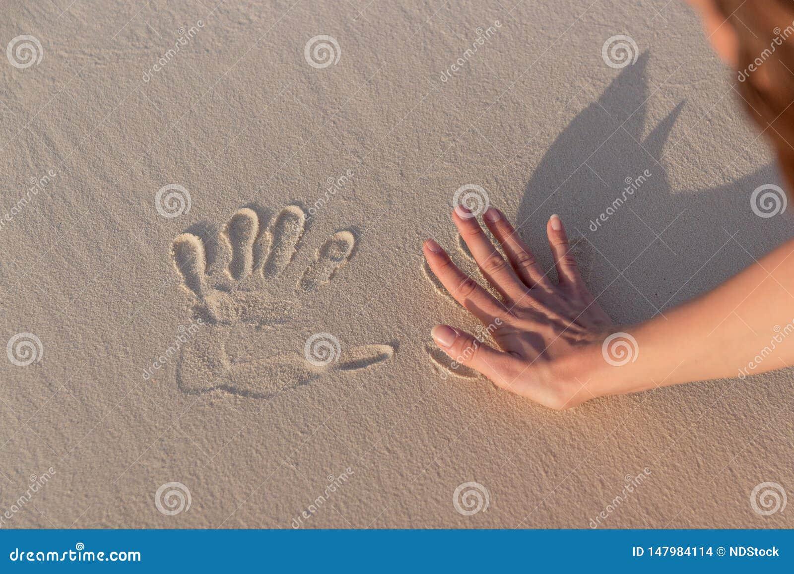 Jonge vrouw die Handprints in wit zand doen