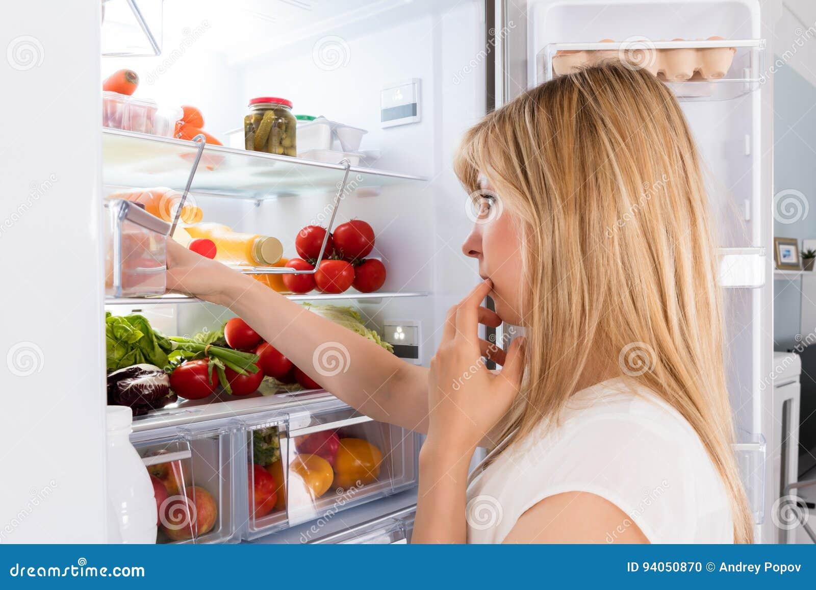 Jonge vrouw die in koelkast kijkt