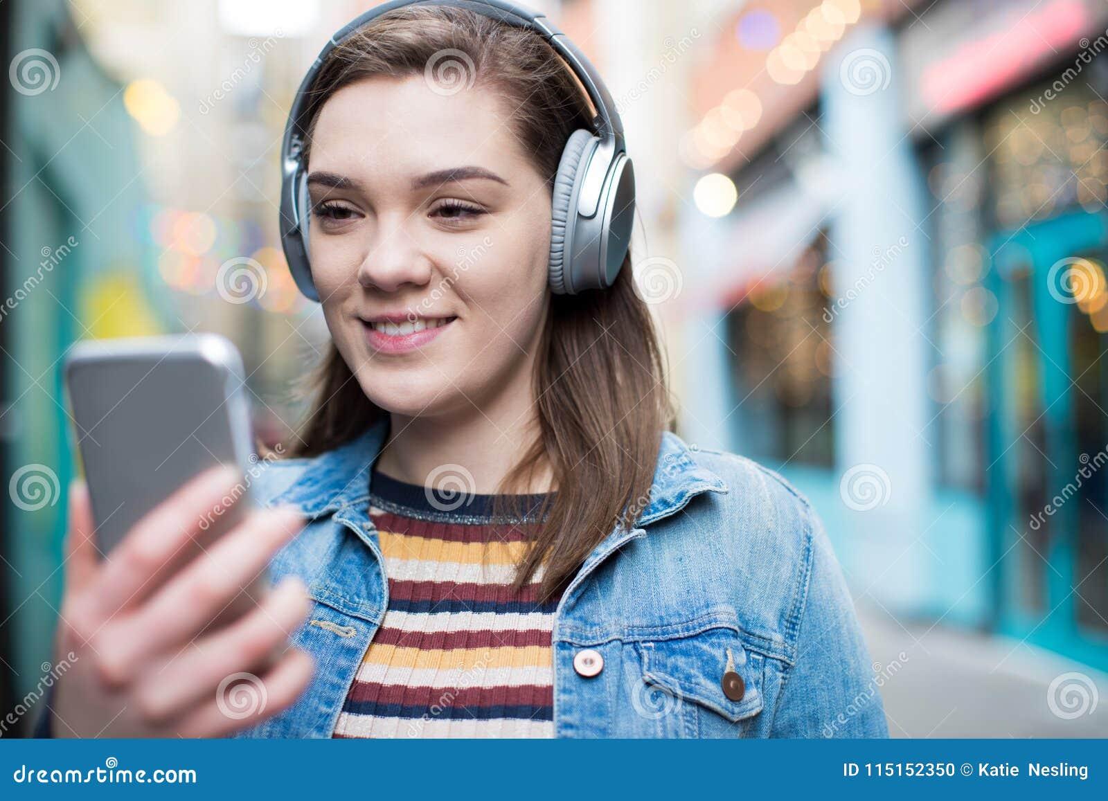 Jonge Vrouw die langs Straat het Stromen Muziek van Mobiele Pho lopen