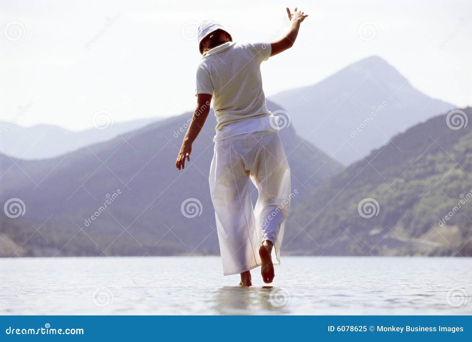 Jonge vrouw die in meer loopt