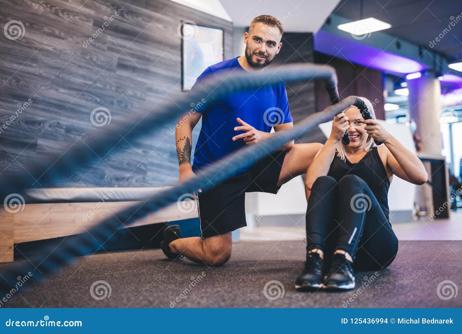 Jonge vrouw die met persoonlijke trainer bij de gymnastiek uitoefenen
