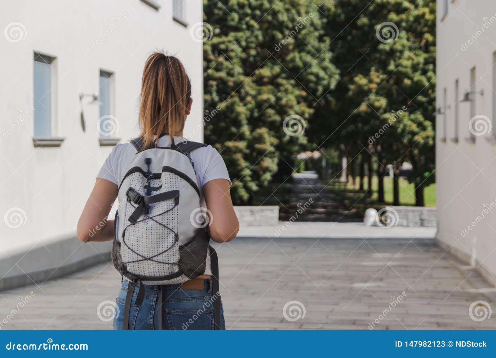 Jonge vrouw die met rugzak aan school na de zomervakantie lopen