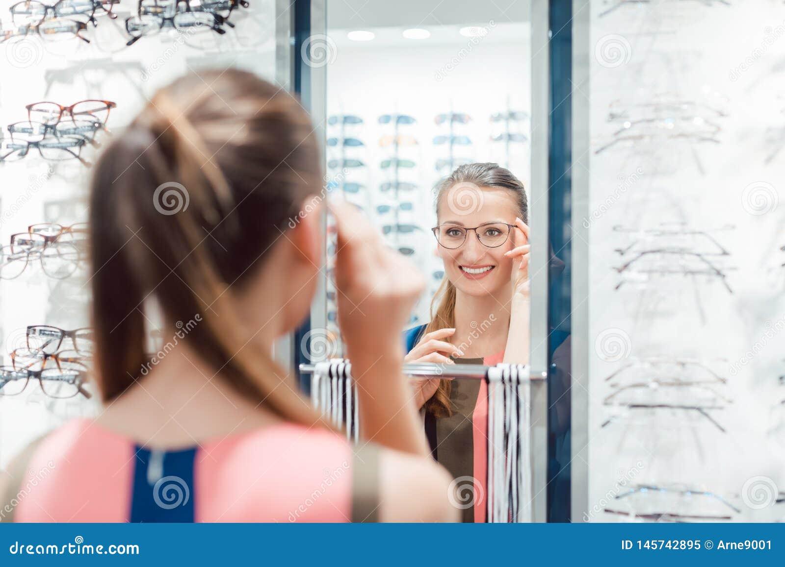Jonge vrouw die modieuze glazen in optometristopslag proberen