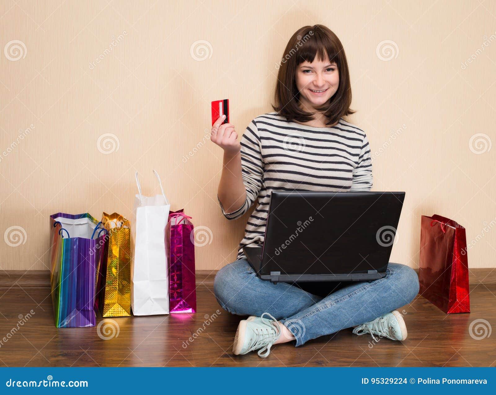 Jonge vrouw die online thuis winkelen Het meisje met het winkelen zakken zit