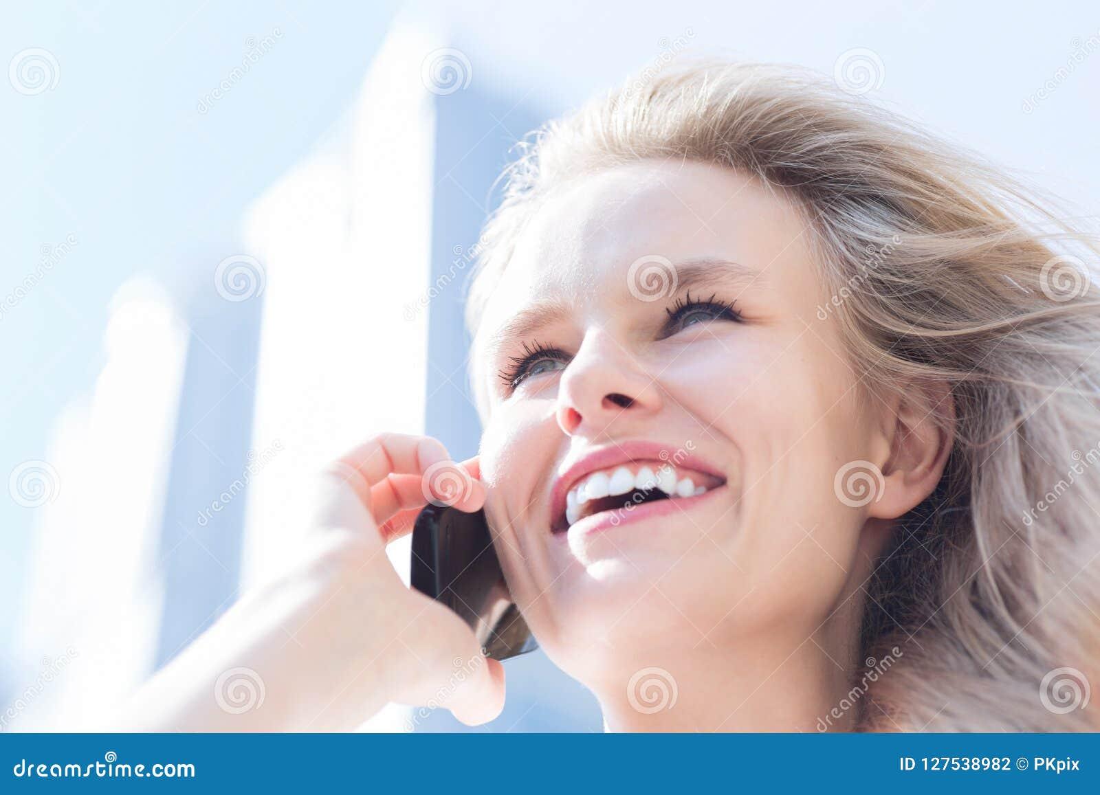 Jonge vrouw die op cellphone over stadsachtergrond spreken Zaken