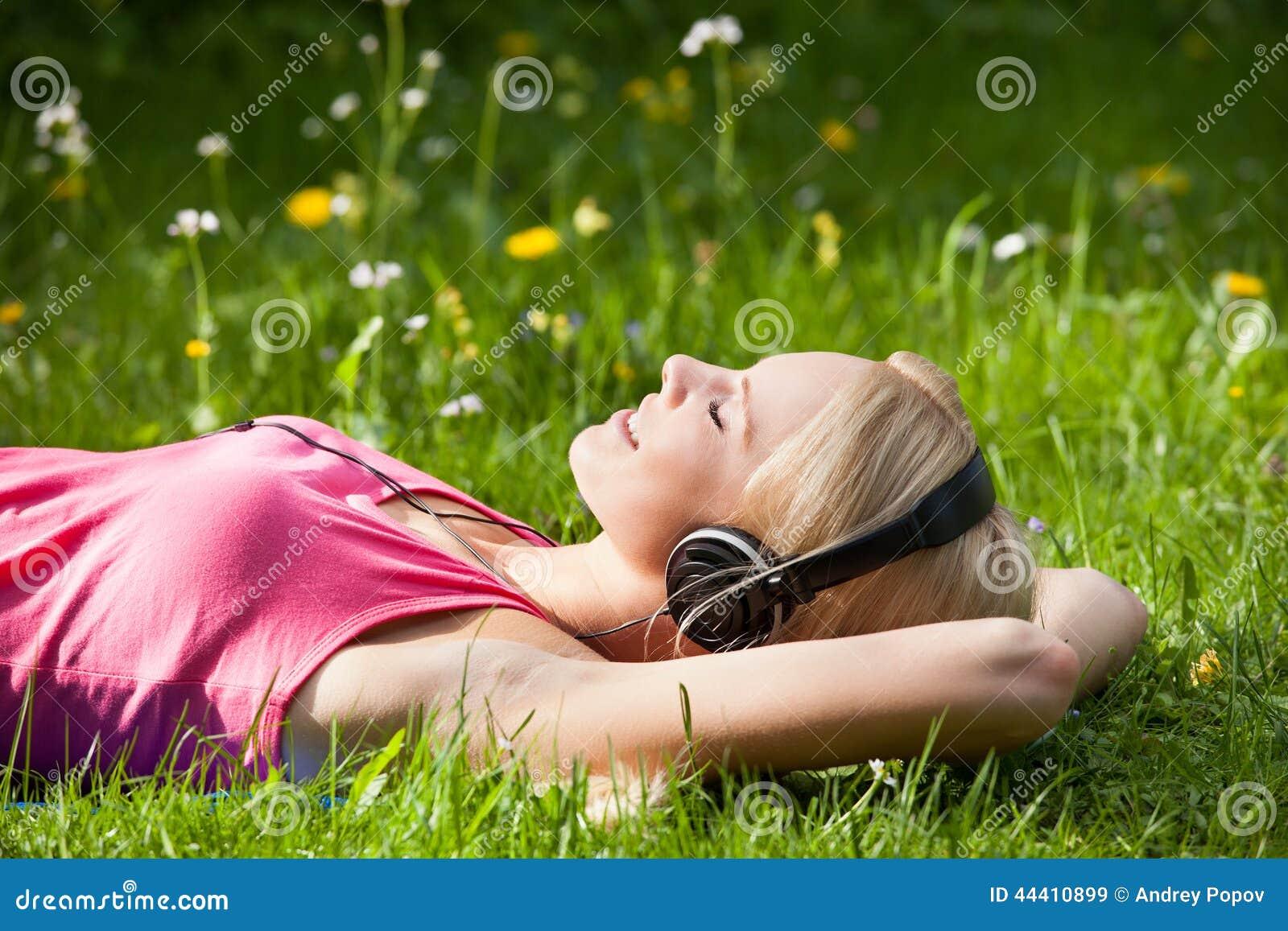 Jonge vrouw die op gras liggen en aan muziek met hoofdtelefoons luisteren
