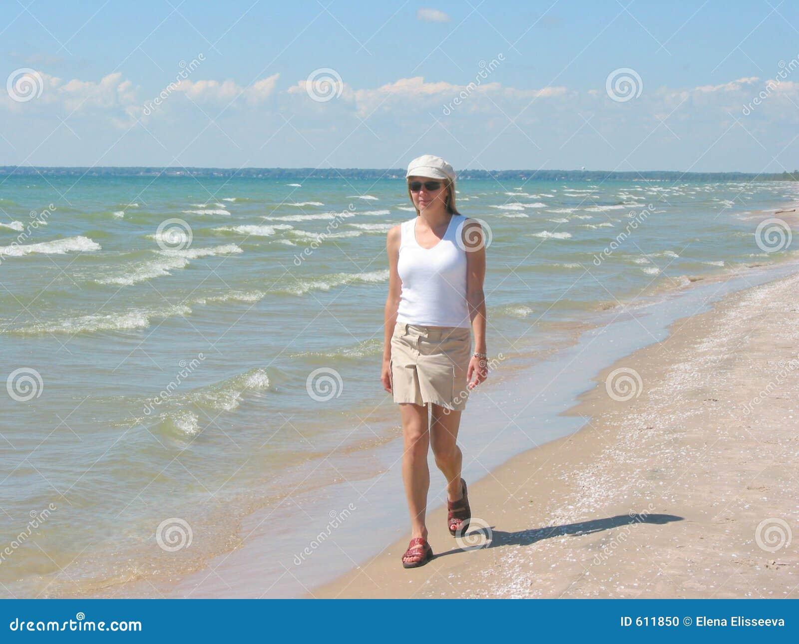 Jonge vrouw die op het strand loopt