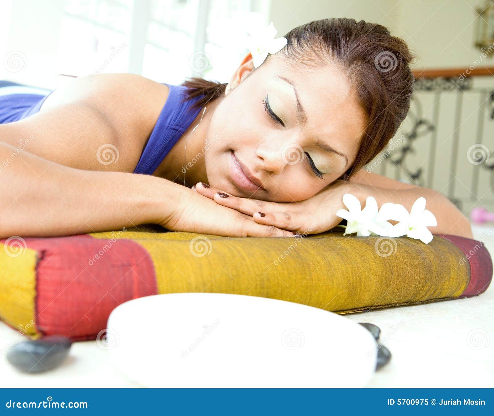 Jonge vrouw die op massagebed rust
